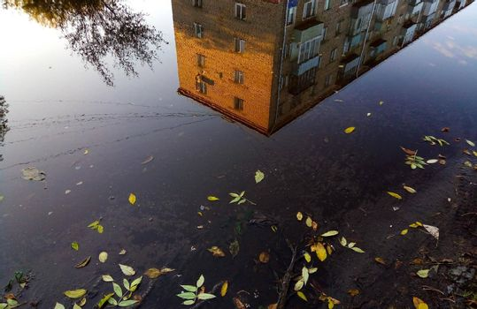 A large autumn puddle reflects the sky and an apartment building.