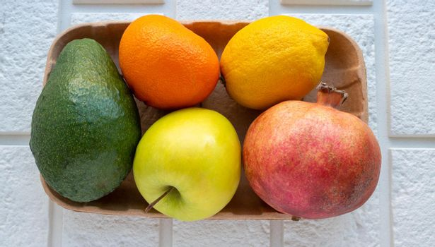 A small collection of fresh fruits in eco-friendly packaging on a white brick background.