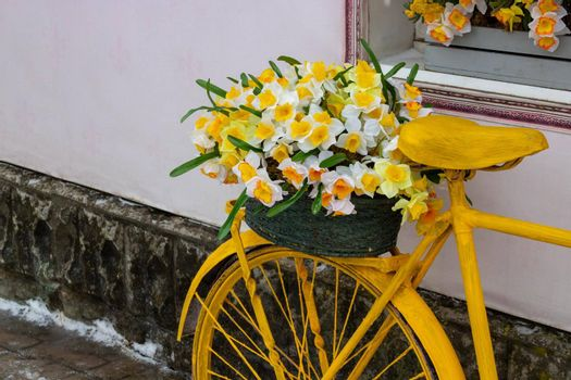 A yellow bicycle wheel with a basket of flowers stands against the wall, in a vintage style.