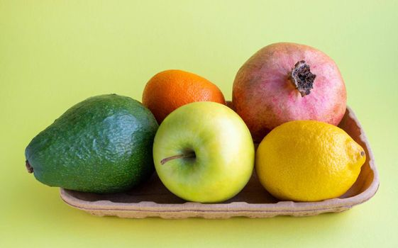 A small collection of fresh fruits in eco-friendly packaging on a yellow background.
