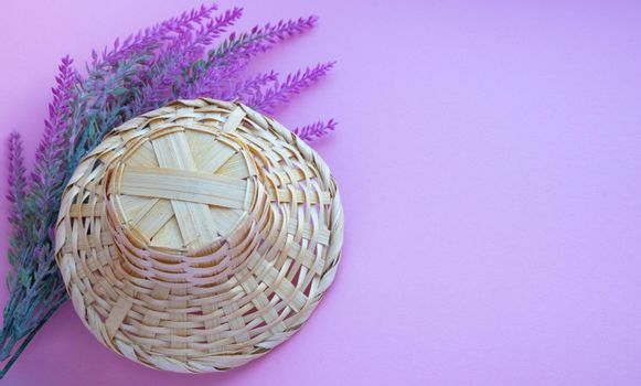 A basket in the shape of a hat lies on a branch of artificial lavender on a pink background. Space for your text.