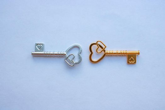 Gold and silver keys, with hearts isolated on a white background.