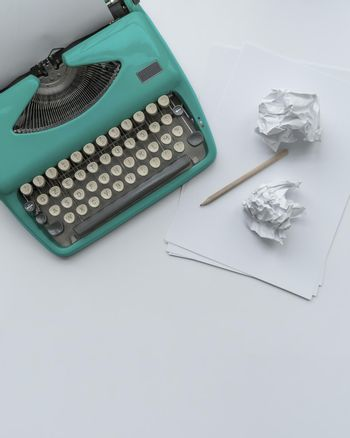A vintage typewriter with paper sheets, stencil and paper balls.