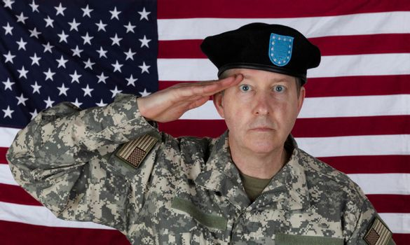Man saluting while wearing military outer shirt and beret with US flag in background