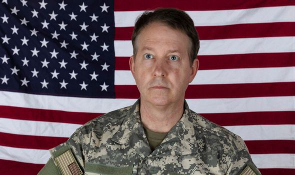 Man wearing military outer shirt without cap with US flag in background