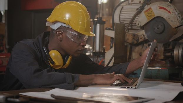 worker man with yellow helmet and ear protection typing keyboard of laptop computer