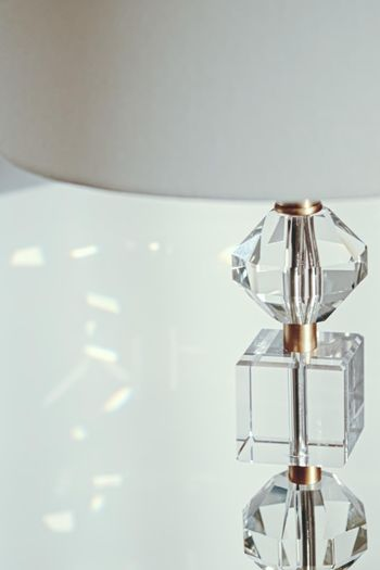 Gold and crystal details of a bedside lamp with shadows at sunset, luxury home decor
