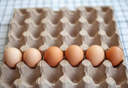 Several brown eggs lie in a row in a large cardboard bag, a chicken egg as a valuable nutritious product, a tray for carrying and storing fragile eggs