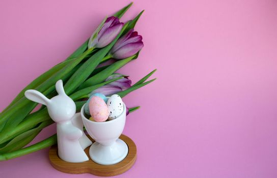 White rabbit, Easter eggs and lilac tulips on pink background, Easter celebration concept.