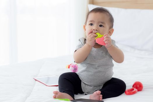 Portrait of cute little baby girl sitting with cozy on bed at bedroom, happiness of toddler, newborn 6-11 months with innocence and expression with cheerful, child charm, indoors, one person.