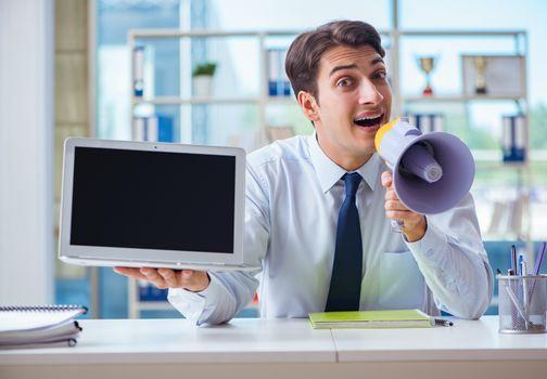 Businessman with loudspeaker presenting at his laptop