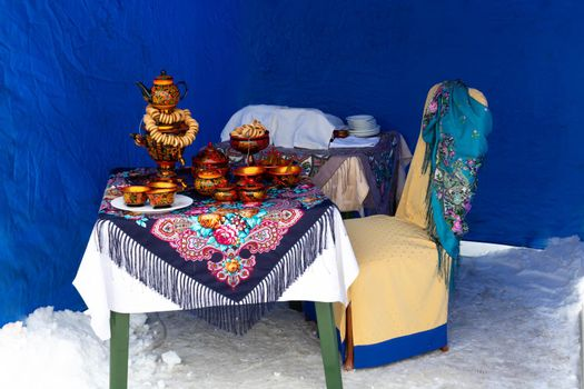 On the table on a colorful tablecloth is a traditional Russian samovar. Russian national tea ceremony.