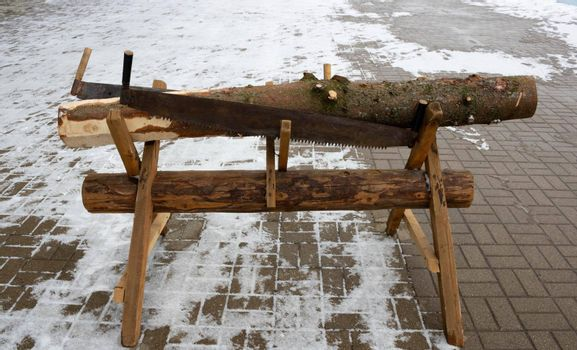 A wooden trestle with a coniferous log and two hand saws on it.