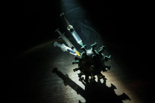 Corona virus Vaccine concept with syringe and green Corona virus novel miniature. Vaccine Concept of fight against coronavirus. Creative decoration with fog and backlight. Selective focus