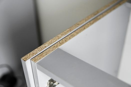 Details of custom kitchen cabinets of the gray modular kitchen from chipboard material on a various stages of installation.