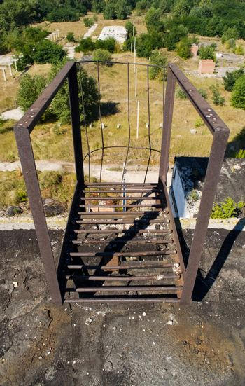old rusty staircase to the roof of the building. Abandoned industrial object.