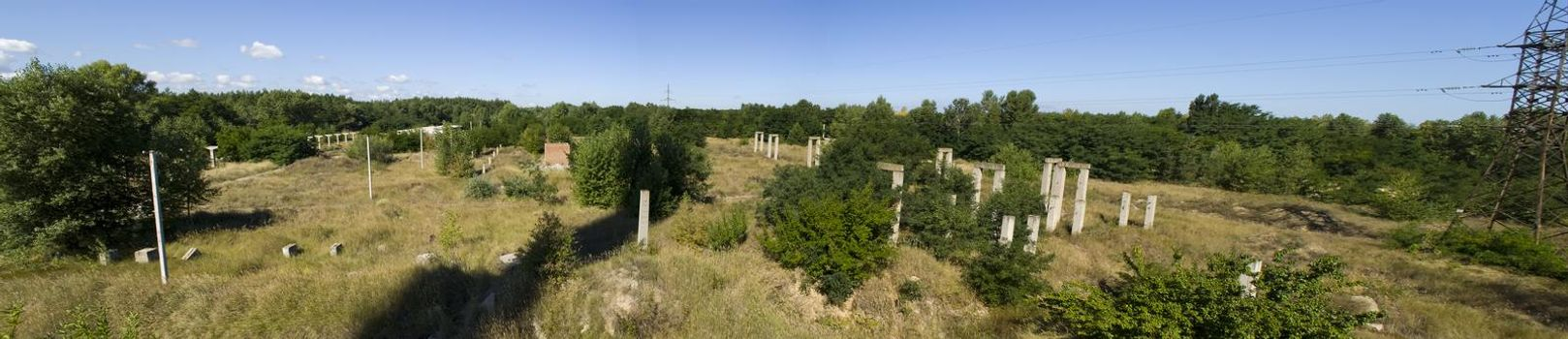 panorama of piles of destroyed buildings overgrown with grass and trees.