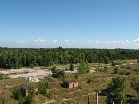 View from above on site with old destroyed buildings, overgrown grass and trees.