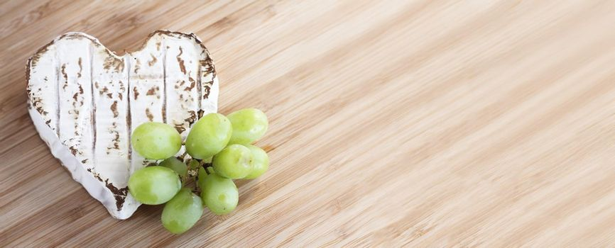 Love cheese concept, Neufchatel cheese shaped like heart with grapes on wooden cutting board , top view flat lay with copy space for text