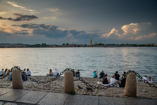 Russia, St.Petersburg, 09 June 2020: People sit on the river bank Neva and observe a sunset on the river water area overlooking a gold spike of the Peter and Paul Fortress, improbable clouds