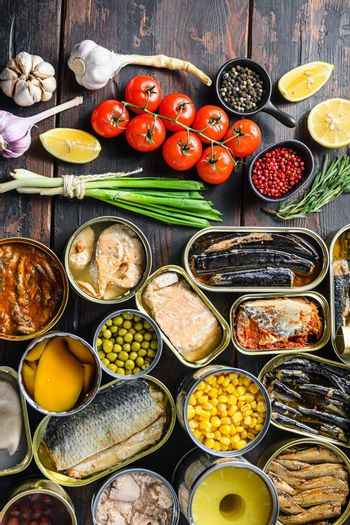 Different canned conserve products in tin cans. with fresh organic ingridients Saury, mackerel, sprats, sardines, pilchard, squid, tuna pinapple, corn, peas, mango , beans, over old wood dark textured background top view