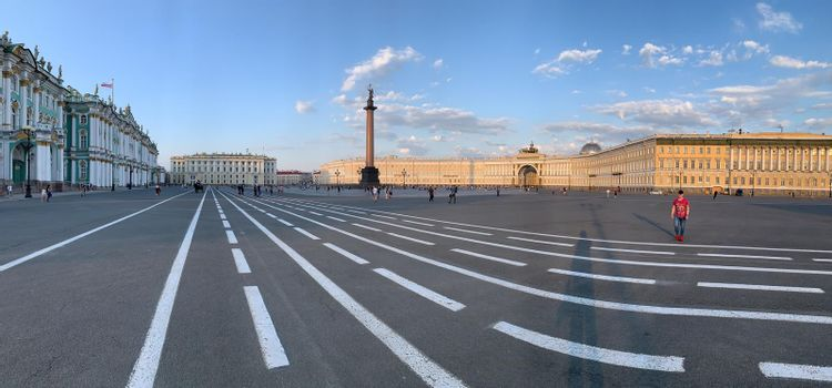 Russia, St.Petersburg, 09 June 2020: Specular panoramic image of the Palace square at sunset, residents walk across square, the Alexandria column on a background