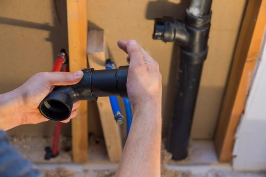 Plumber joining PVC sewage drain pipes on a home under construction