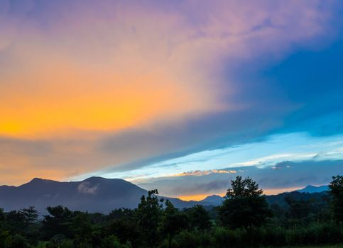 Colorful Sky and Clouds drifting over the forest mountain in evening time