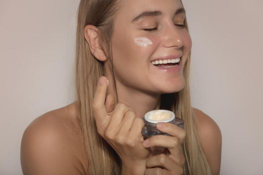 Portrait of a Nice Female with Closed Eyes of Pleasure Applying Moisturizer Cream on Face. Natural Cosmetics. Isolated on Beige Background. Beauty and Health Care.