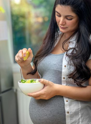 Portrait of a Nice Pregnant Woman with Pleasure Eating Fresh Green Salad at Home. Healthy Nutrition for Future Mom. Happy Healthy Pregnancy Time.