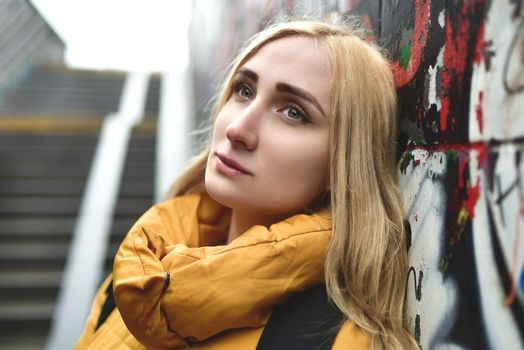 Portrait of a beautiful, pretty, attractive teenage blonde with a pensive look leaning back against a graffiti-painted wall outdoors, close-up