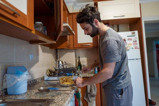one attractive guy preparing breakfast and brunch with french fries in his house because of being hungry