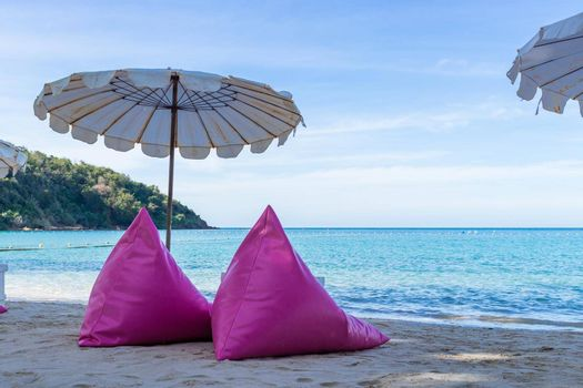Pink inflatable sofa on the beach.