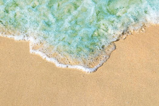 Soft waves with foam of blue ocean on the sandy beach