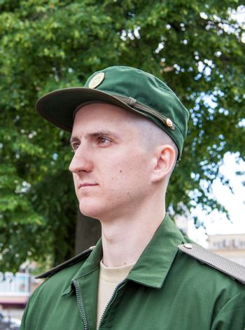 Portrait of a young soldier in uniform. The oath of a young recruit to the ranks of the Russian Army.