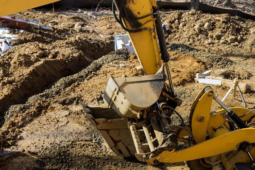 Excavator dig trench at construction site laying sewer wells pipes sewage drainage system
