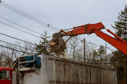 Dismantling an old house, bulldozer destroys of the demolition of a building under construction of a new house.