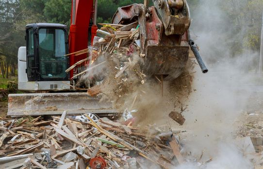 Demolition work ruined residential excavator with hydraulic crusher wooden house after tornadoes came through