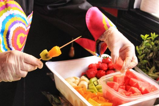 Cook hands with gloves preparing colorful fruit skewers