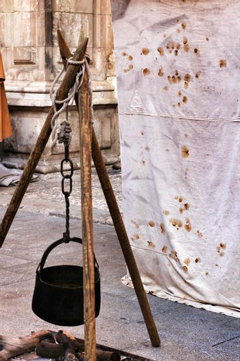 Black Iron cauldron hanging on a bonfire at a medieval market in Elche
