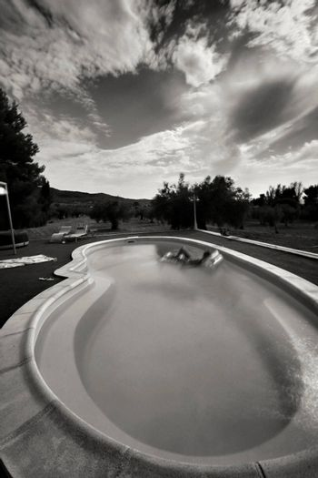 Large oval pool with mountains views under cloudy sky in Spain