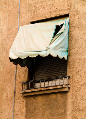 Old window with broken green awning
