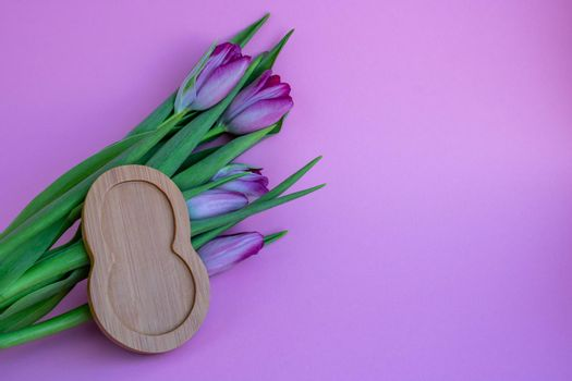 Tulips on a pink background and 8 made of wood.Concept March 8.
