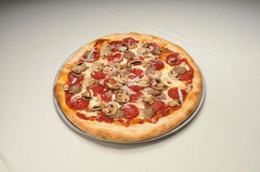 Delicious tomato sauce cheese covered hot and tasty Pepperoni Sausage Mushroom Onion pizza pie