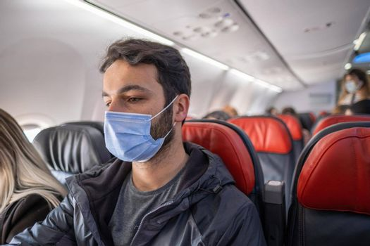 handsome brown-haired man with mask sits on a plane seat in quarantine days with copy space
