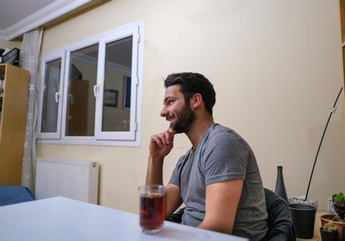 black bearded man sitting on chair in living room and having conversation with his friends