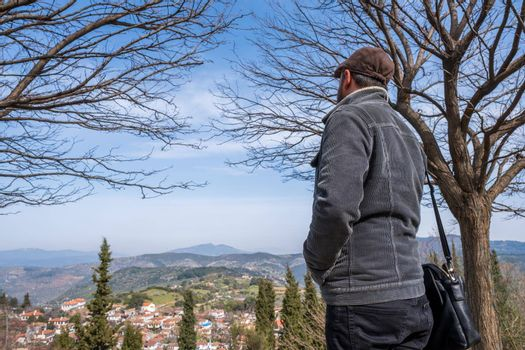 attractive man in 30s looks at landscape from a hill