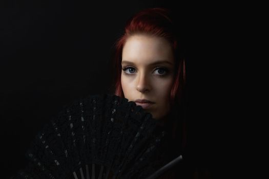 Low key portrait of beautiful young woman with fan.