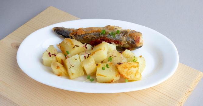 Fried fish and potatoes on a white plate on the table.