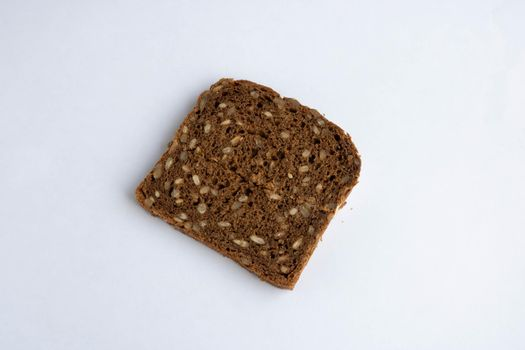 Slice of whole-grain dark bread, isolated on a white background close-up.